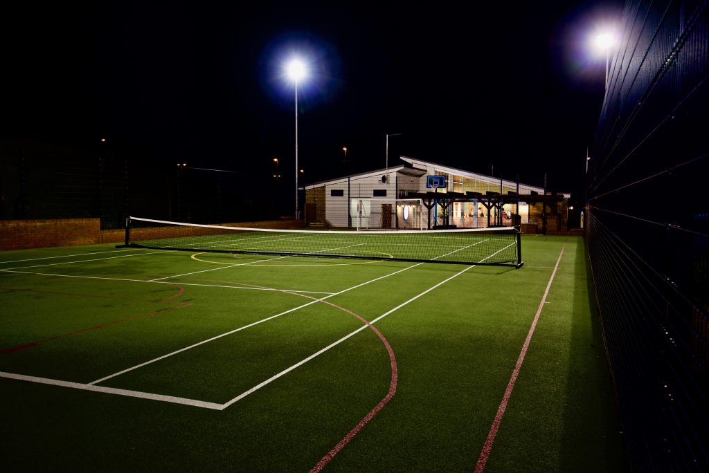 Outdoor sports court at night with fllodlights